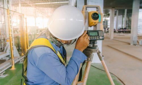 ingegnere-dell-ispettore-che-fa-misurare-con-l-attrezzatura-del-teodolite-al-cantiere_29285-1484